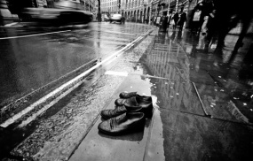 Two-pair-of-old-shoes-try-to-cross-Regent-street-London-on-a-rainy-day