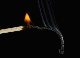 Burnout concept. Closeup of burning match, black background.
