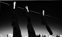 pair-of-black-socks-and-an-odd-one-hanging-on-a-washing-line-with-blue-sky-over-a-city-skyline-joe-fox